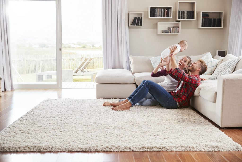 Young white couple play with their toddler in sitting room