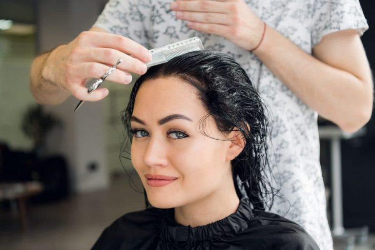Hairdresser cutting woman's hair in salon, smiling, front view, close-up, portrait